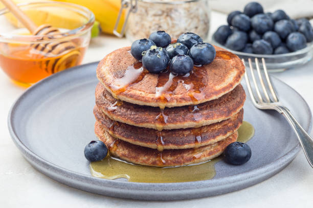 Healthy oatmeal banana pancakes garnished with blueberry and honey, on gray plate, horizontal stock photo