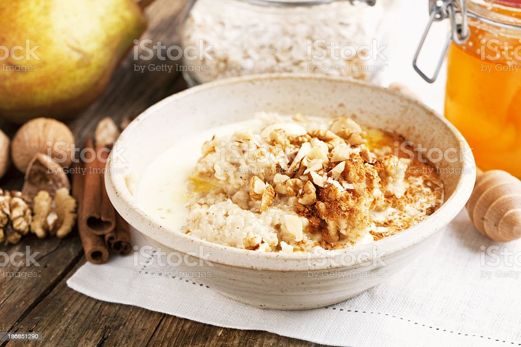 healthy oatmeal with cream, honey and walnuts stock photo