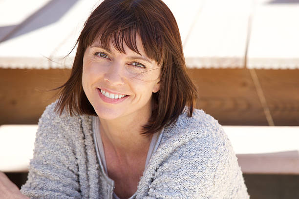 Healthy older woman smiling outside Close up portrait of a healthy older woman smiling outside 40 44 years stock pictures, royalty-free photos & images