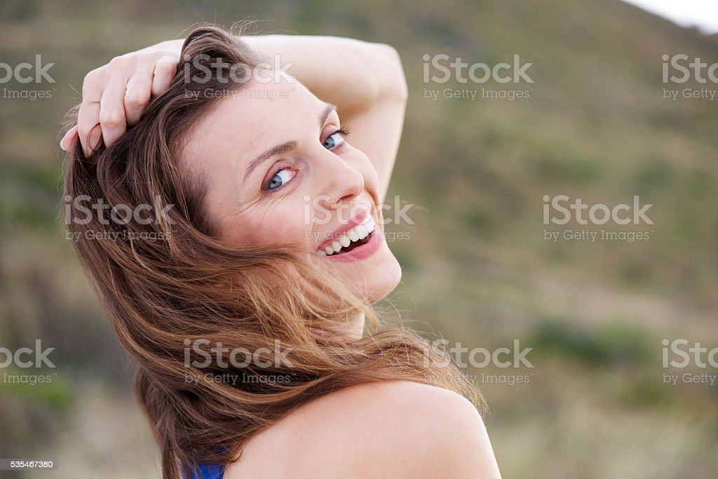 Healthy older woman smiling outside with hand in hair stock photo