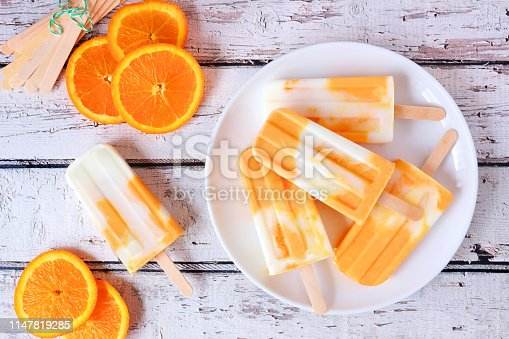 Healthy orange yogurt ice pops on a plate, top view table scene against a white wood background