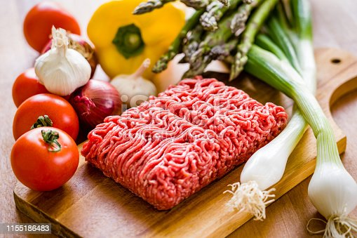 Organic ground beef and pork on a wooden cutting board in a table top in the kitchen surrounded by fresh vegetables.