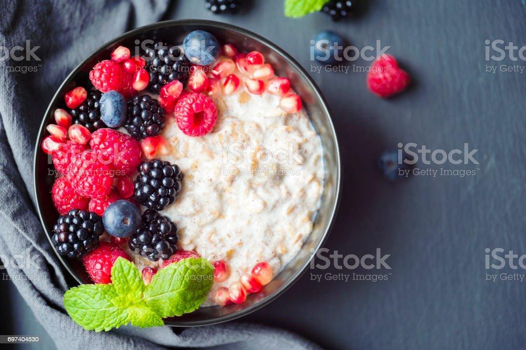 Healthy organic porridge topped with berries stock photo