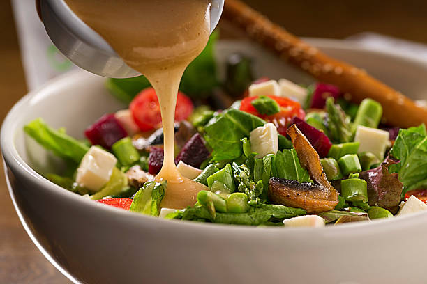 Healthy Organic Salad Organic green salad with lettuce, asparragus, beets, tomato,mushroom, fresh white cheese and vinaigrette dressing. salad dressing stock pictures, royalty-free photos & images