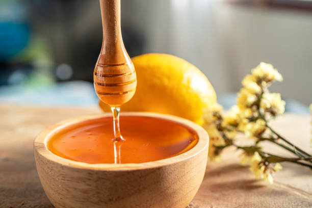 Healthy organic scoop Thick honey dipping with wooden honey spoon from a wooden bowl, honey dripping, pouring honey into the bowl. Close-up. stock photo