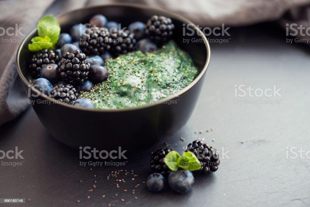 Healthy organic spirulina porridge topped with berries stock photo