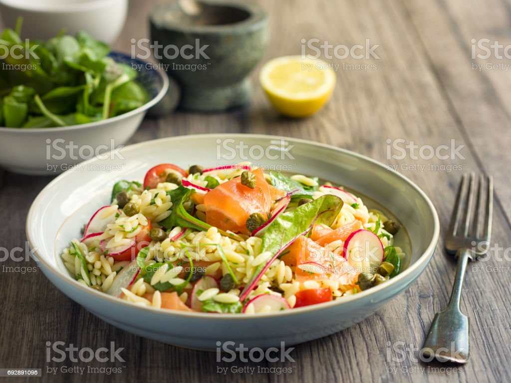 Healthy orzo salad with smoke salmon stock photo