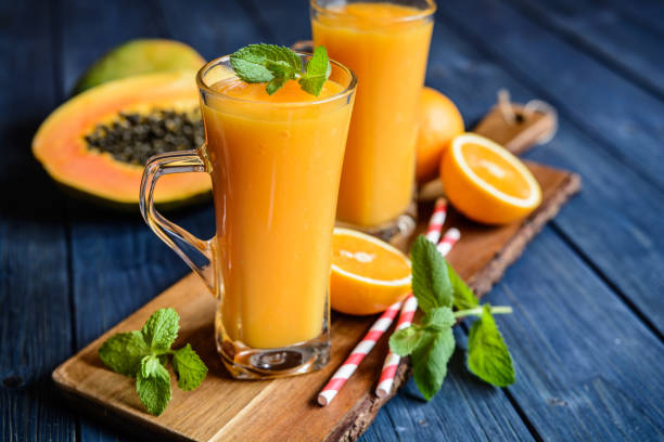 Healthy papaya, orange and mango smoothie Healthy papaya, orange and mango smoothie in a glass jar papaya smoothie stock pictures, royalty-free photos & images