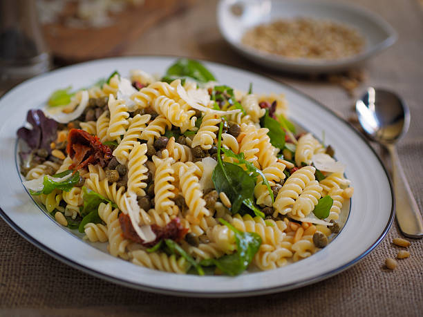Healthy pasta salad Home made healthy fusilli pasta salad with capers,sun dried tomatoes and shaved pamesan cheese fusilli stock pictures, royalty-free photos & images