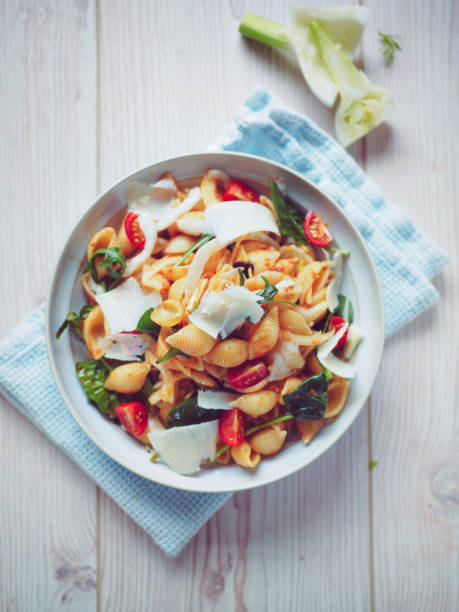 Healthy pasta salad Home made Healthy pasta salad,mix with orecchiette pasta with red pesto sauce,cherry tomatoes and rocket leaves,sliced fennel,service with shaven  parmesan cheese. orecchiette stock pictures, royalty-free photos & images