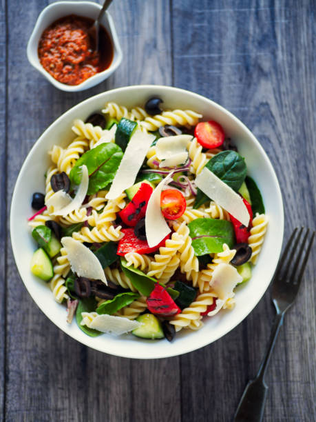 Healthy pasta salad Home made healthy pasta salad,mix cooked pasta with cucumber,cherry tomatoes,freshness leaves and black olives,grilled red pepper.service with red pesto sauce and shaved parmesan cheese fusilli stock pictures, royalty-free photos & images