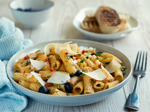 Healthy Pasta salad Home made freshness rigatoni pasta salad with red pesto chilli sauce and black olives,service with shaved parmesan cheese and  toasted ciabatta bread rigatoni stock pictures, royalty-free photos & images