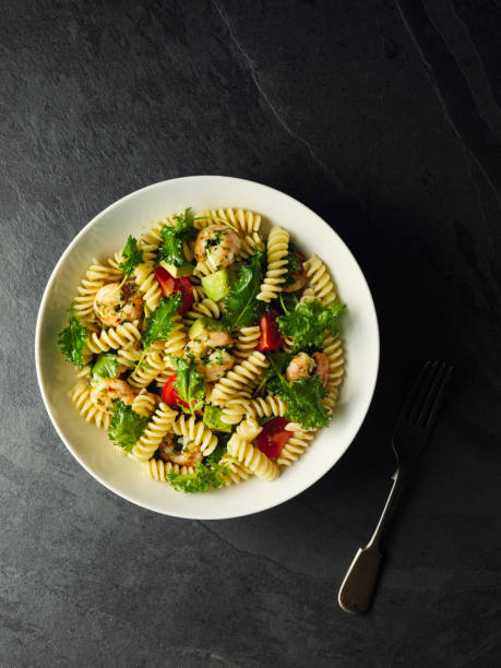 Healthy pasta salad with grilled king prawn Home made freshness fusilli pasta with cherry tomatoes,avocado,and wild kale with green pesto sauce and grilled king prawn. fusilli stock pictures, royalty-free photos & images