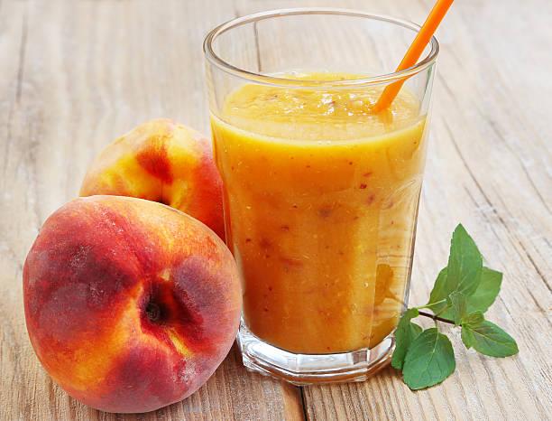 gesunde peaches-smoothie in glas - pfirsich milchshake stock-fotos und bilder