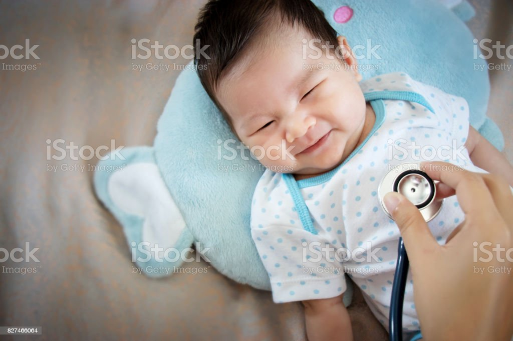 healthy people concept. Asian adorable baby infant laughing with happy face for good health on doctor check up time stock photo