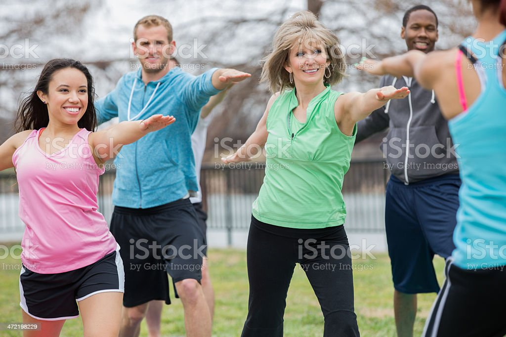 Healthy people stretching together during outdoor yoga exercise class stock photo