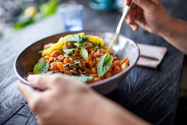 persona sana comiendo ensalada de garbanzos orgánicos de tazón con tenedor en el restaurante bohemio rústico - vegana fotografías e imágenes de stock