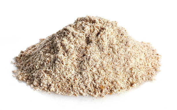 Healthy plain whole wheat flour that can be used for baking Small mound of whole wheat flour on a white background with natural shadow. See other varieties of grains in my FOOD ISOLATED  lightbox. burwellphotography stock pictures, royalty-free photos & images