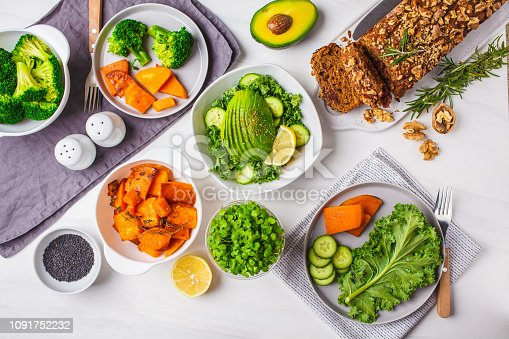istock Healthy plant based food lunch, top view. Green salad, sweet potato, vegan cake, vegetables on white background. 1091752232