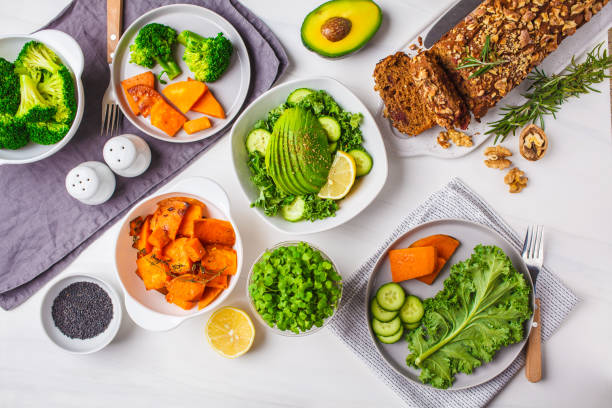 Healthy plant based food lunch, top view. Green salad, sweet potato, vegan cake, vegetables on white background. stock photo