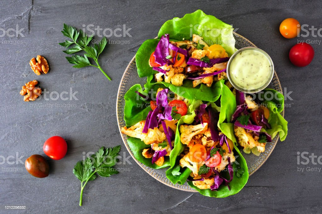 Healthy plant based lettuce wraps with grilled cauliflower, top view over a dark slate background Healthy lettuce wraps with grilled cauliflower, cabbage and tomatoes. Top view over a dark slate background. Plant-based diet concept. Above Stock Photo
