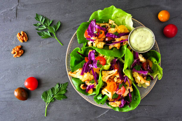 Healthy plant based lettuce wraps with grilled cauliflower, top view over a dark slate background stock photo