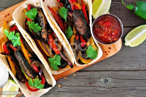 Portobello mushroom vegan fajitas. Close up top view on a wood background. Healthy eating, plant-based meat substitute concept.
