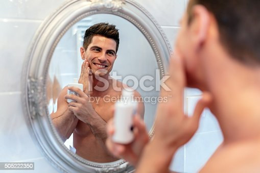istock Healthy positive male treating sking with lotion 505222350