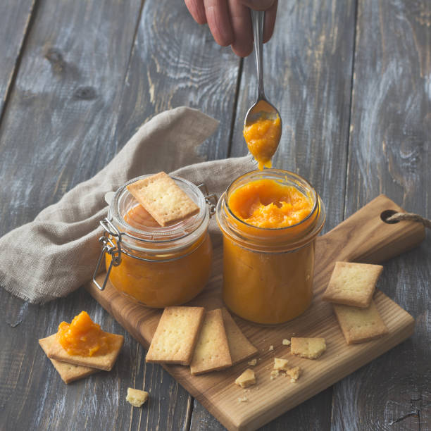 Healthy raw orange jam with dried apricots in a glass jar with cookies on a wooden table stock photo