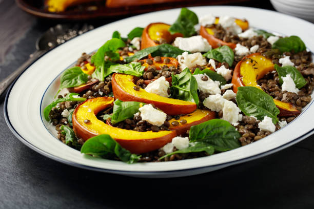 healthy roasted pumpkin wedges with green lentils and goat cheese - lenticchie verdi foto e immagini stock