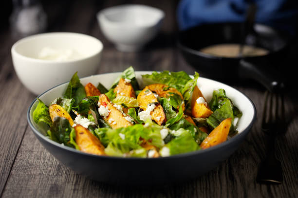 Healthy roasted sweet potatoes salad Home made freshness roasted sweet potatoes, cos lettuce and feta cheese flakes, pumpkin seeds sweet potato stock pictures, royalty-free photos & images