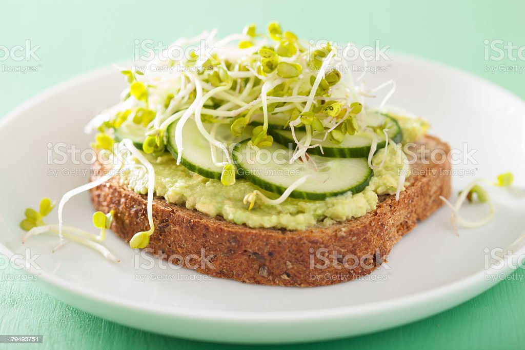 healthy rye bread with avocado cucumber radish sprouts stock photo