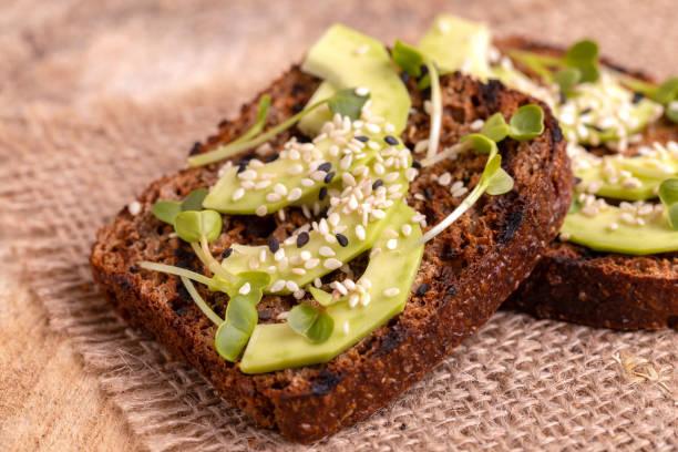 Gesund Roggen Toast mit Avocado, Rettich-Sprossen und Sesam auf Sackleinen Serviette – Foto
