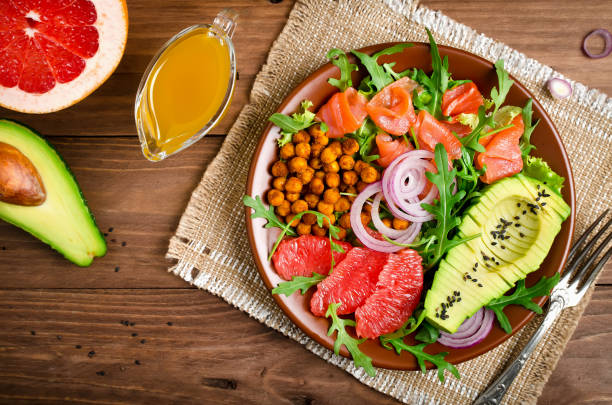 Healthy salad bowl with salmon, grapefruit, spicy chickpeas, avocado, red onion and arugula stock photo