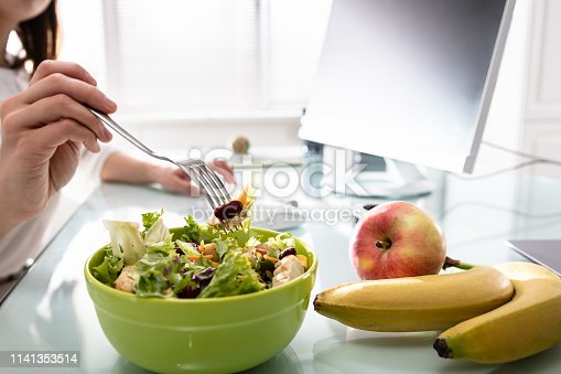 Close-up Of Woman's Hand Holding Fork While Having Healthy Salad On Office Desk