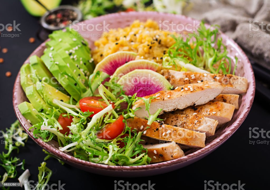 Healthy salad with chicken, tomatoes,  avocado, lettuce, watermelon radish and lentil on dark background. royalty-free stock photo