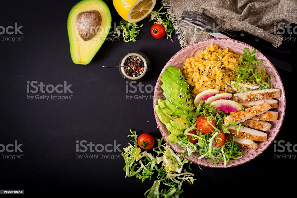Healthy salad with chicken, tomatoes,  avocado, lettuce, watermelon radish and lentil on dark background. Flat lay. Top view royalty-free stock photo