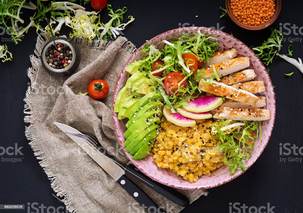 Healthy salad with chicken, tomatoes,  avocado, lettuce, watermelon radish and lentil on dark background. Flat lay. Top view foto stock royalty-free