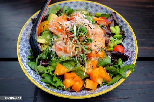 Close up shot of healthy salad bowl with sliced raw salmon ,avocado, mango and leaf vegetables above dark wooden table