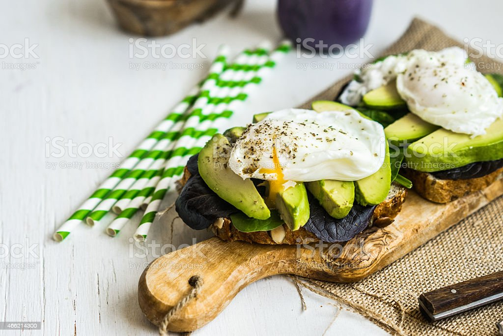 Healthy sandwich with avocado and poached eggs stock photo