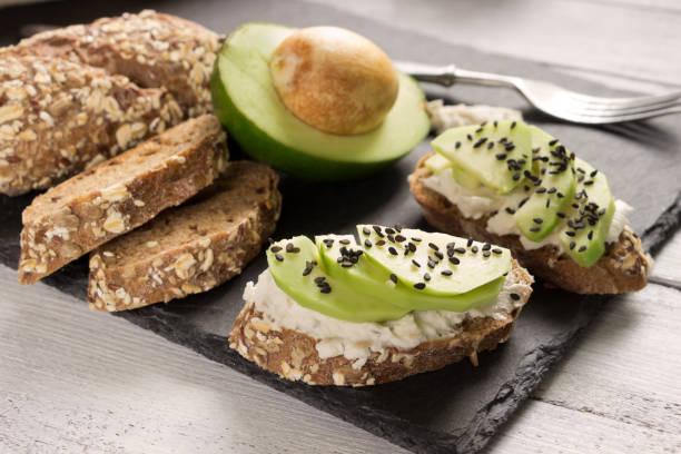 sándwiches saludables con aguacate, queso y pan integral. saludable desayuno servido en mesa de madera de piedra pizarra, blanco - pan multicereales fotografías e imágenes de stock