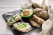 Healthy sandwiches with avocado, cottage cheese and whole wheat bread. Healthy breakfast served on black stone board ,white wooden table