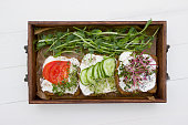 Healthy sandwiches with cream cheese , microgreens, tomatoes and cucumber in  wooden box. Healthy eating concept , diet food, vegan food, healthy breakfast.White wooden board