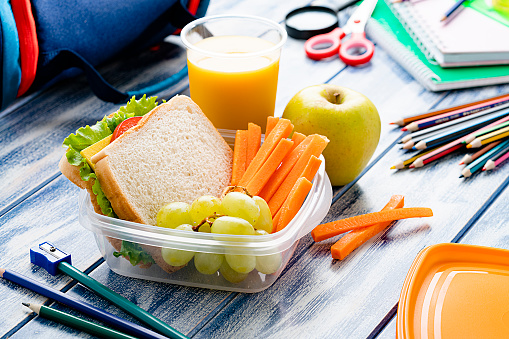 Healthy food for kids concepts: well balanced school lunch box shot on blue table. School supplies are around the lunch box. High resolution 42Mp studio digital capture taken with SONY A7rII and Zeiss Batis 40mm F2.0 CF lens