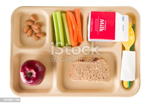An overhead close up of a tray containing a healthy school lunch. It consists of crunchy peanut butter and jelly sandwich on whole wheat multigrain bread, celery sticks, carrot sticks, almonds, a red apple and milk. Isolated on white.