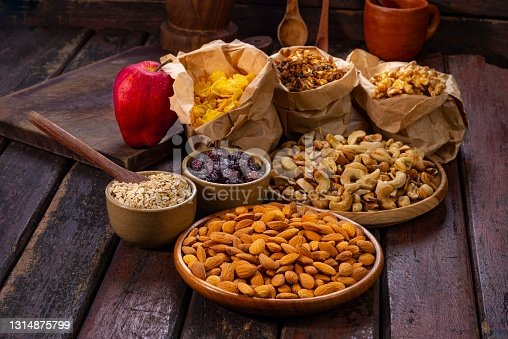 Healthy food ingredients on rustic table of wood for breakfast. In the image are oats flakes, almonds, walnuts,cashews,corn flakes and a red apple fruit.