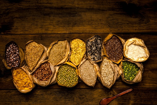 High angle view of healthy seed, grain and flake in small brown paper bags. In the paper bags are flaxseed or linseed, wheat, oats flakes, white rice, integral rice, sunflower seeds, alpist or birdseed or alpist or canary stone, cornflakes, kidney beans, lentils, slipt green peas, green peas and roasted coffee beans.\nImage made in studio using a Nikon 24 megapixels full size sensor.