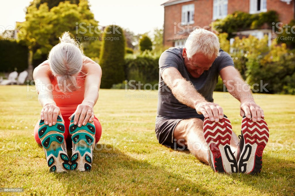 Healthy Senior Couple Exercising In Garden Together стоковое фото