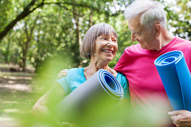 Healthy senior couple with yoga mat in the park stock photo