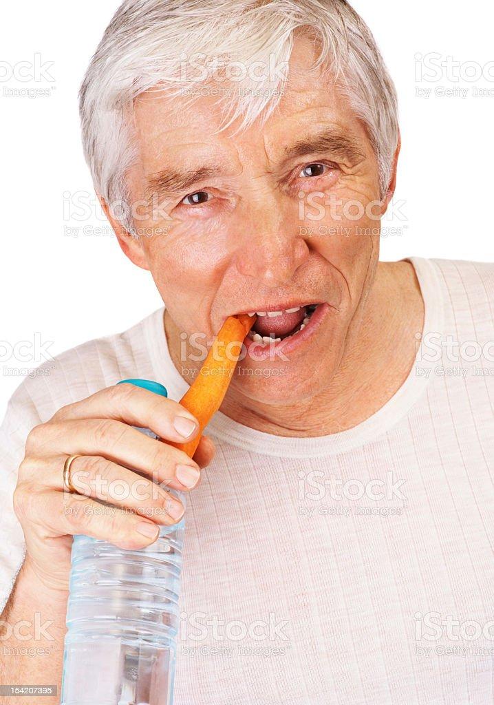 Healthy senior man eating a carrot royalty-free stock photo